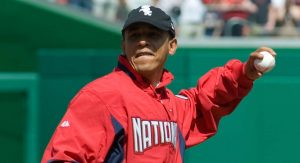 Obama wearing Barack Obama hat while being a pitcher in a baseball game