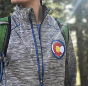 A man wears jacket in the forest on Colorado day