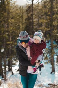 Mom and daughter wearing Colorado hat in snowy forest