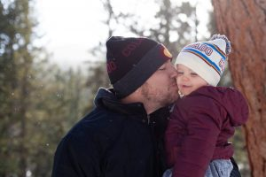 Father and son kissing while wearing colorado hat beanie
