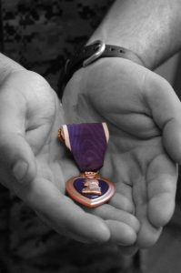 Hands hold The Purple Heart Medal