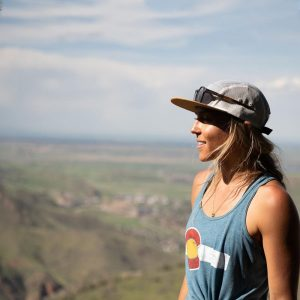 Girl wears a tank top at the peak of mountain on Colorado day