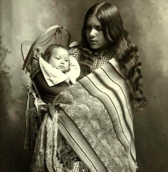 A girl wearing American Indian Blankets and holding a baby