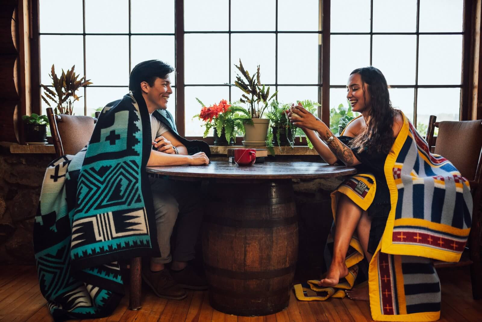 A couple wearing American Indian blankets indoor