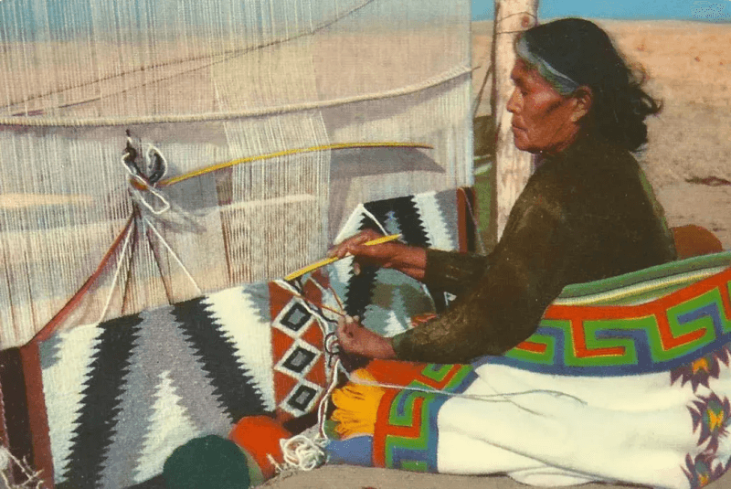A woman makees Navajo American Indian blankets