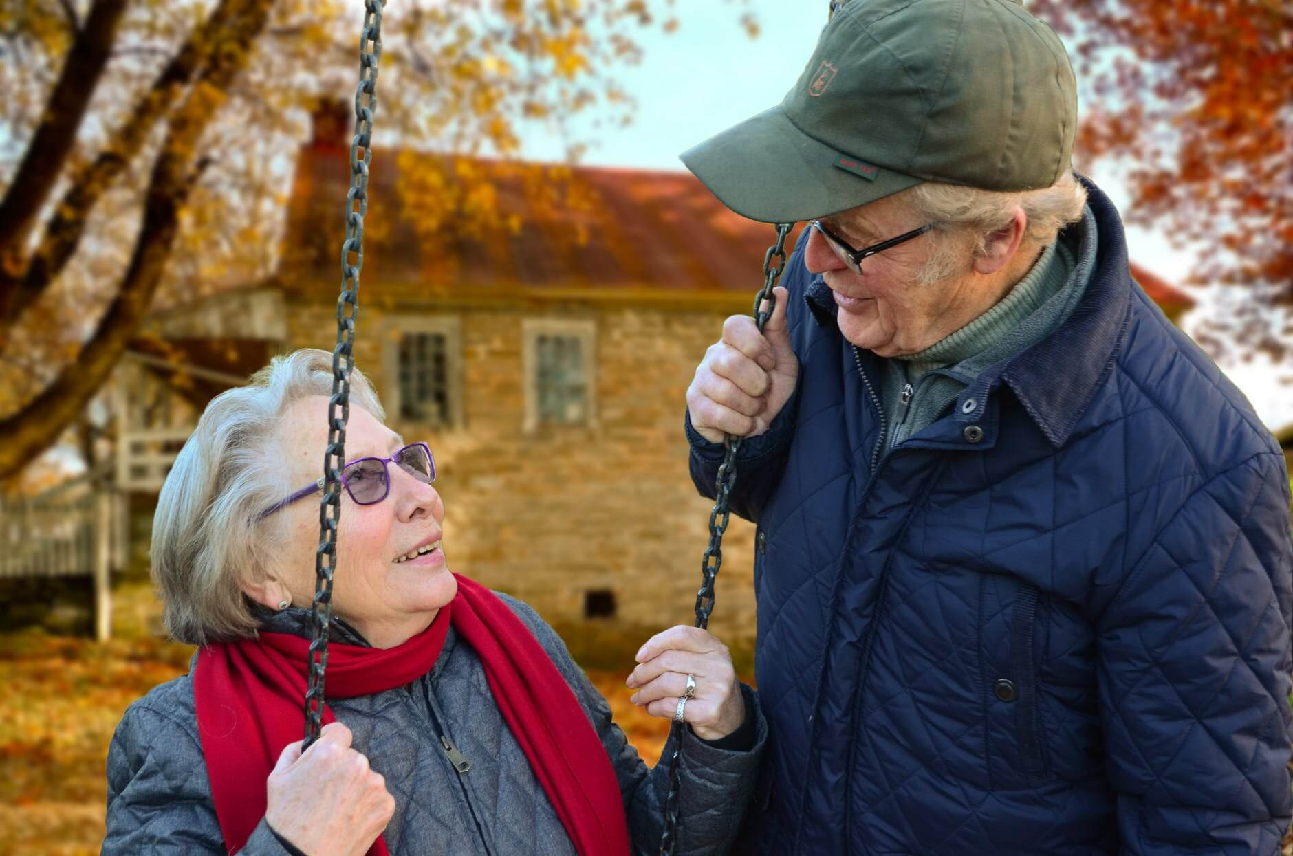 Old couple grandparents happy while playing swing in autumn